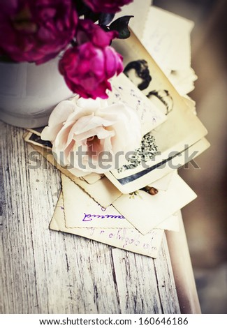 Beautiful roses with old letters and postcard on wooden background/ nostalgic romantic background