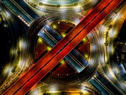 Beautiful roundabout intersection at night view. Aerial view of circle transportation in the city with colorful light. Drone view from night sky.