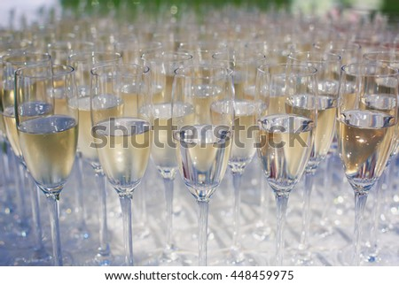 Beautiful row line of gold yellow colored glasses with champagne on a party, on decorated catering bouquet table on open air event, picture with beautiful bokeh  #448459975