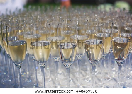 Beautiful row line of gold yellow colored glasses with champagne on a party, on decorated catering bouquet table on open air event, picture with beautiful bokeh  #448459978