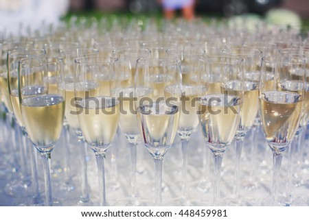 Beautiful row line of gold yellow colored glasses with champagne on a party, on decorated catering bouquet table on open air event, picture with beautiful bokeh  #448459981