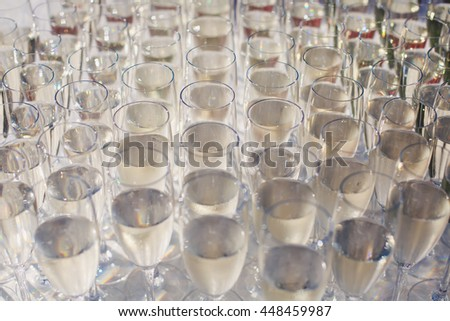 Beautiful row line of gold yellow colored glasses with champagne on a party, on decorated catering bouquet table on open air event, picture with beautiful bokeh  #448459987