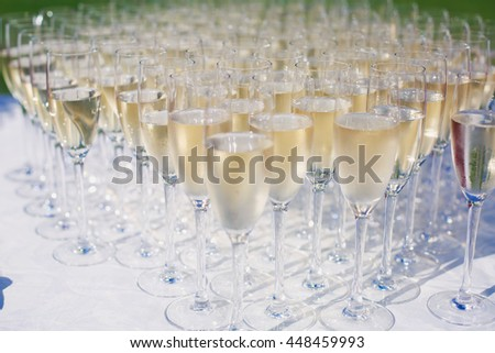 Beautiful row line of gold yellow colored glasses with champagne on a party, on decorated catering bouquet table on open air event, picture with beautiful bokeh  #448459993