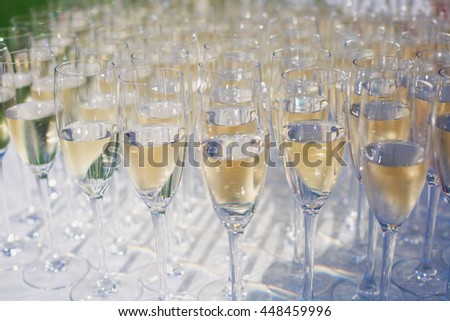 Beautiful row line of gold yellow colored glasses with champagne on a party, on decorated catering bouquet table on open air event, picture with beautiful bokeh  #448459996