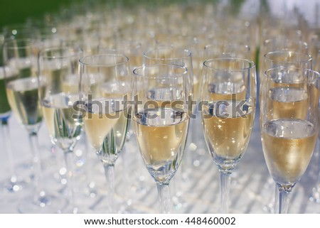 Beautiful row line of gold yellow colored glasses with champagne on a party, on decorated catering bouquet table on open air event, picture with beautiful bokeh  #448460002