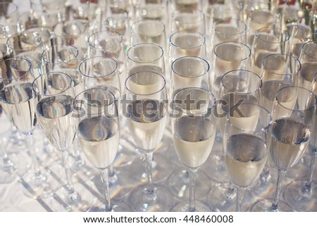 Beautiful row line of gold yellow colored glasses with champagne on a party, on decorated catering bouquet table on open air event, picture with beautiful bokeh  #448460008