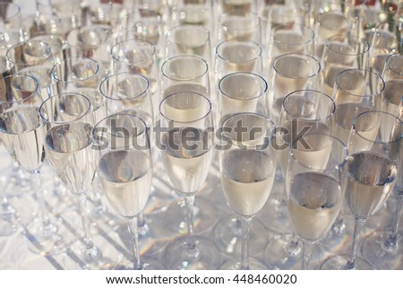Beautiful row line of gold yellow colored glasses with champagne on a party, on decorated catering bouquet table on open air event, picture with beautiful bokeh  #448460020