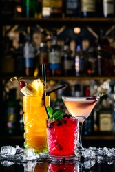 beautiful row line of three different colored alcohol cocktails on bar in nightclub copyspace