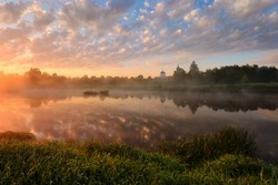 Beautiful rural landscape in morning fog at sunrise. Temple on the river bank at sunrise, reflected in the river. Traditional Russian landscape. Klyazma River, Moscow Region, Russia