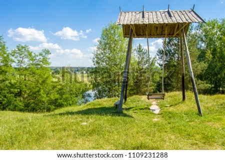 Beautiful rural landscape river Teteriv (Teterev). On steep mountain face steeper swing -  wooden structure with bench where children were playing, in background - houses of village and river bed #1109231288