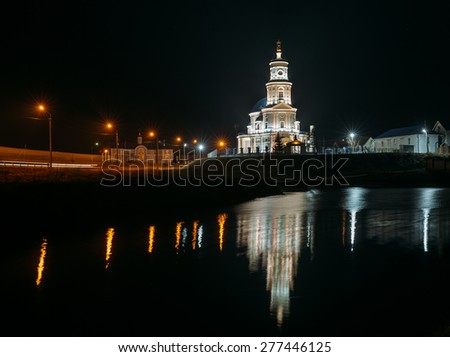 Beautiful Russian Christian church on the banks of the river at night in windy weather .