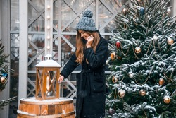 Beautiful russian girl in a cloud day in winter clothes with christmas ball in hands having fun in Tverskaya Square in Christmas time