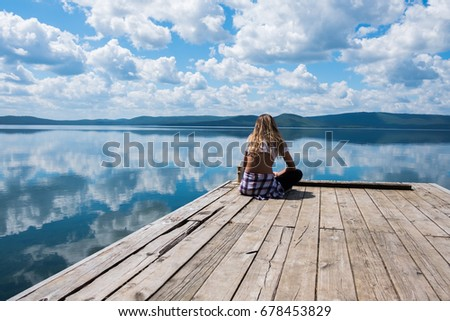 beautiful russian woman on the lake is relaxing