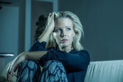 beautiful 40s woman depressed at home - dramatic portrait of sad and desperate blonde girl on couch suffering depression problem and anxiety crisis feeling helpless and lonely