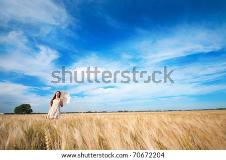 Beautiful sad and lonely woman with umbrella walking in wheat field. Timed.