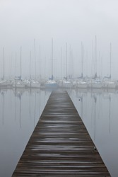 Beautiful sailboat harbor in the fog with wooden pier and reflections in lake