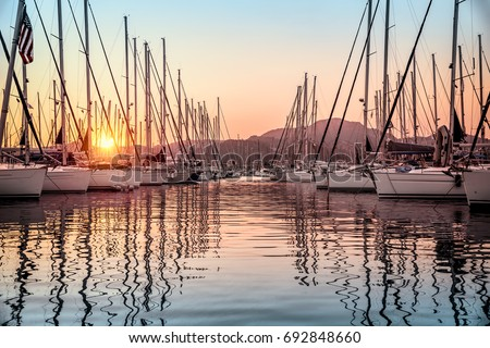 Beautiful sailboats moored in the dock, amazing view of gorgeous white sail boats over mountains background in mild sunset light, luxury summer vacation in Marmaris, Turkey