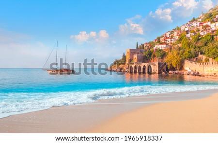 Beautiful sandy beach and soft turqoise Mediterranean sea wave - Landscape of ancient shipyard near of Kizil Kule tower - Alanya peninsula, Turkey