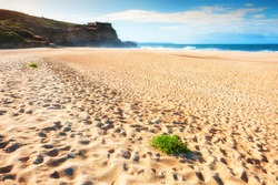 Beautiful sandy beach in Nazare, Portugal. Waves on the coast of Atlantic ocean. Famous travel destination