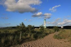 beautiful sandy beach path with dune landscae and lighthouse by the Baltic Sea