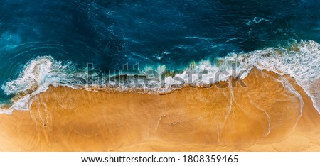 Photo of  Beautiful sandy beach, top view. Panoramic view of the sandy beach. The sea wave rolls on the shore. Sea coast view from the air. Aerial photography of the sea wave. The ocean and beach. Copy space