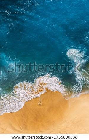 Beautiful sandy beach with blue sea, vertical view. Drone view of tropical blue ocean beach Nusa penida Bali Indonesia. Lonely sandy beach with beautiful waves. Beaches of Indonesia. Copy space