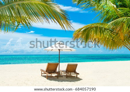 Beautiful sandy beach with sunbeds and umbrellas in Indian ocean, Maldives island #684057190