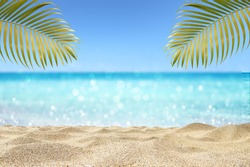 beautiful sandy beach with tropical palm leaf on blur ocean background summer concept