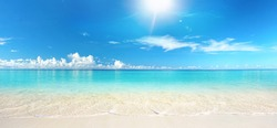 Beautiful sandy beach with white sand and rolling calm wave of turquoise ocean on Sunny day on background white clouds in blue sky. Island in Maldives, colorful perfect panoramic natural landscape.