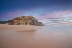 Beautiful sandy ocean beach and cliff at the sunset. Panorama atlantic coastline.