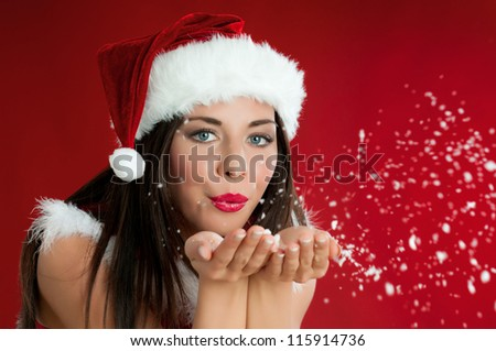 Beautiful santa claus girl blowing white snowflakes from her hands on red christmas background