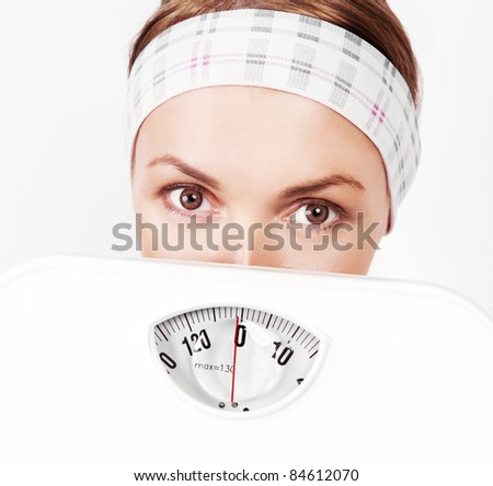 beautiful scared young blond sporty woman  holding scales