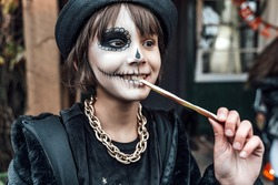Beautiful scary little girl celebrating halloween, chewing gummy worm. Terrifying face makeup and witch costume, stylish image. Horror, fun at children's party in barn on street. Hat, fur coat, chain.