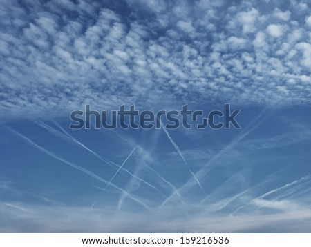 Beautiful scattered clouds structure over deep blue sky with jet trails