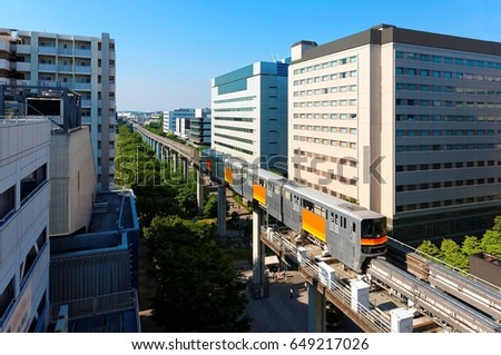 Beautiful scenery of a train traveling on elevated tracks of Tama Toshi Monorail (Route connecting Higashiyamato & Tama) between office blocks in Tachikawa , Tokyo, Japan, under blue clear sunny sky #649217026