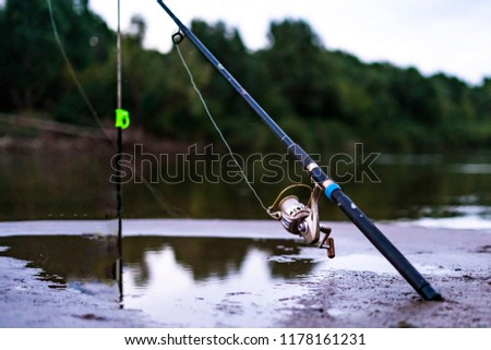 beautiful scenery of fishing concept. fish rod on the sandy river bank at the dusk #1178161231