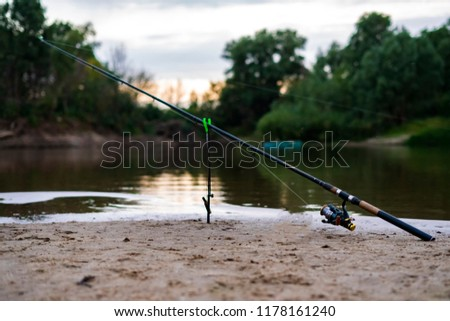 beautiful scenery of fishing concept. fish rod on the sandy river bank at the dusk #1178161240