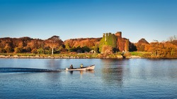 Beautiful scenery of Menlo castle surrounded by a autumn colored trees and boat passing by in Corrib river at Galway, Ireland