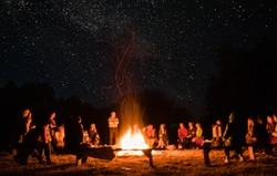beautiful scenery of night vision. bonfire around people. basking by the fire at night. the concept of outdoor activities.