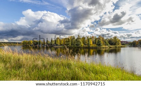 Beautiful scenery of sunny autumn day at the river with expressive cloudy sky. Autumn starts to color the leaves of the trees