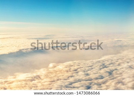 Beautiful scenic dramatic morning sunrise cloudscape aerial view from plane window. Gradient colored fluffy clouds during aircraft flight travel at sunset. Natural sky background #1473086066