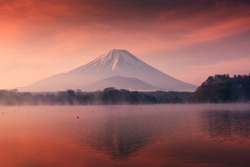 Beautiful scenic landscape of mountain Fuji or Fujisan with reflection on Shoji lake at dawn with twilight sky in Yamanashi Prefecture, Japan. Famous travel and camping in 1 of 5 Fuji lakes.