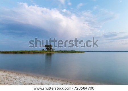 Beautiful scenic landscape of river or lake bank, calm water and island with tree against dramatic cloudy sky. #728584900