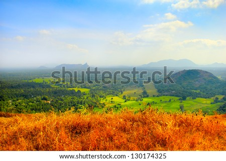 Beautiful scenic landscape of Sri Lanka with dry yellow grass, distant disappear in mist rocks, colorful green fields and wood, view from Yapahuwa Rock, South Asia