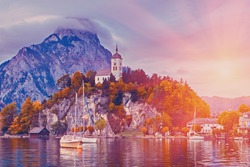 Beautiful scenic sunset over Austrian alps lake. Boats, yachts in the sunlight infront of church on the rock with clouds over Traunstein mountain at the alps lake near Hallstatt, Salzkammergut Austria
