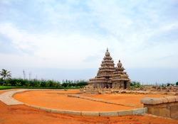 Beautiful scenic view, ancient hindu Sea Shore Temple (UNESCO world heritage site) dedicated to Shiva and Vishnu, against background of cloudy sky in Mamallapuram, Tamil Nadu (Tamilnadu), South India