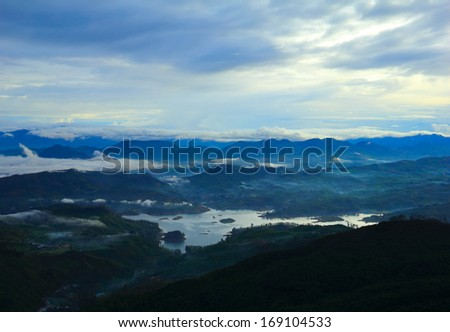 Beautiful scenic view at early morning - shadow figures of fogged mountain tops and serene lake against the background of dramatic blue sky near Sri Pada (Adam's Peak), Sri Lanka island, South Asia  #169104533