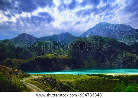 Beautiful scenic view - colorful teal blue water of Toktogul lake under barren mountains against the background of dramatic cloudy sky at evening, Tien (Tian) Shan range, Kyrgyzstan, Central Asia #654733348