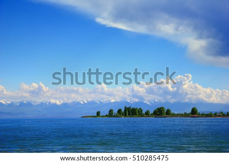 Beautiful scenic view - distant open wood amid the calm water of Issyk-Kul Lake against the background of Tien Shan mountain range and cloudy blue sky, Kyrgyzstan, Central Asia #510285475