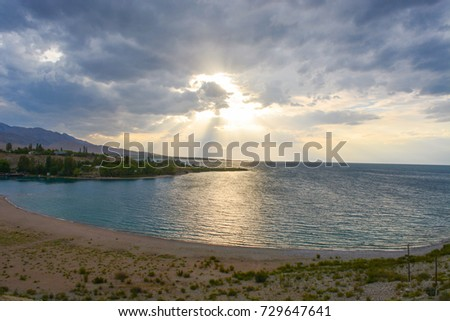 Beautiful scenic view - distant open wood amid the calm water of Issyk-Kul Lake against the background of Tien Shan mountain range and cloudy blue sky, Kyrgyzstan, Central Asia #729647641